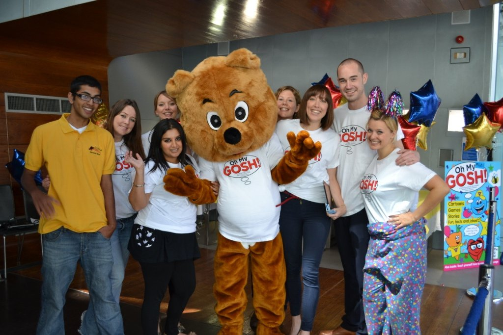 Volunteers and a GOSH bear say Oh My Gosh!