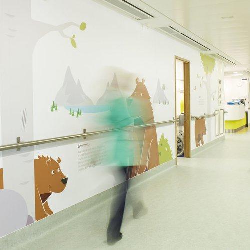 Nurse in green walking along Bear Ward corridor