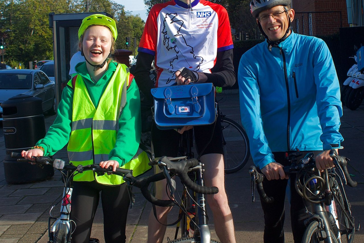 GOSH Young People's Forum Member, Rosie stands with two GOSH staff members, holding their bikes.