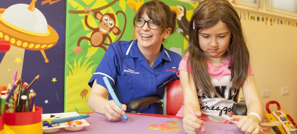 Nurse seated at table assisting young person in drawing exercise