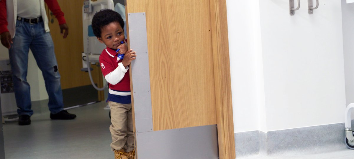 Boy peering round hospital door
