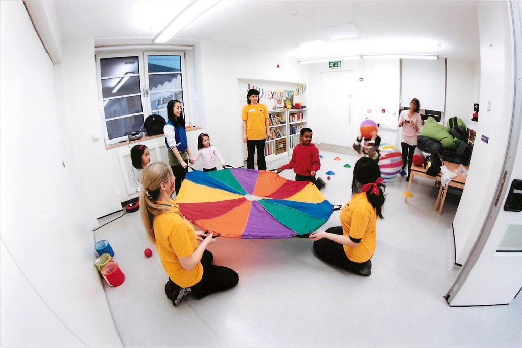 Volunteers and children playing colourful games on a ward