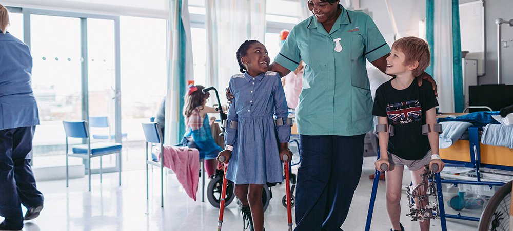 Healthcare assistant with children on Sky Ward