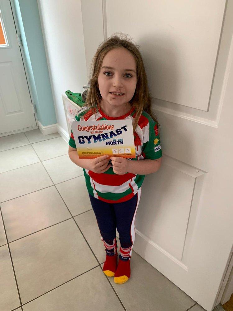 Image of patient Sara with her gymnast award