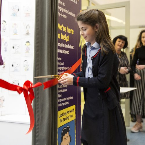 A patient cuts the ribbon, opening the Lucy Booth