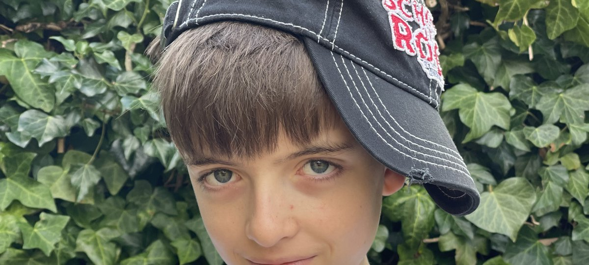 12 year old Oliver wears a School of Rock baseball cap, tilted to the side, with his arms crossed and his hands in a V sign.