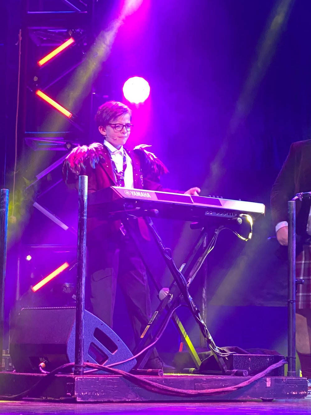 Former GOSH patient, Oliver, as Lawrence in School of Rock the Musical, plays the keyboard in costume, in a live performance.