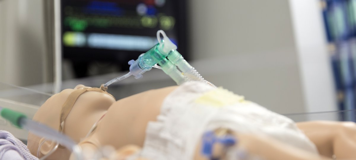 Simulation manikin in front of simulated patient monitor