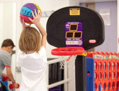 Child playing basketball for physiotherapy