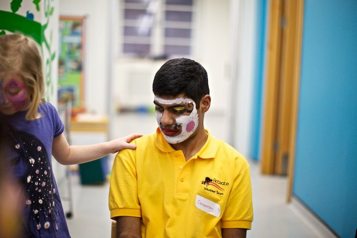 A patient face painting with volunteers